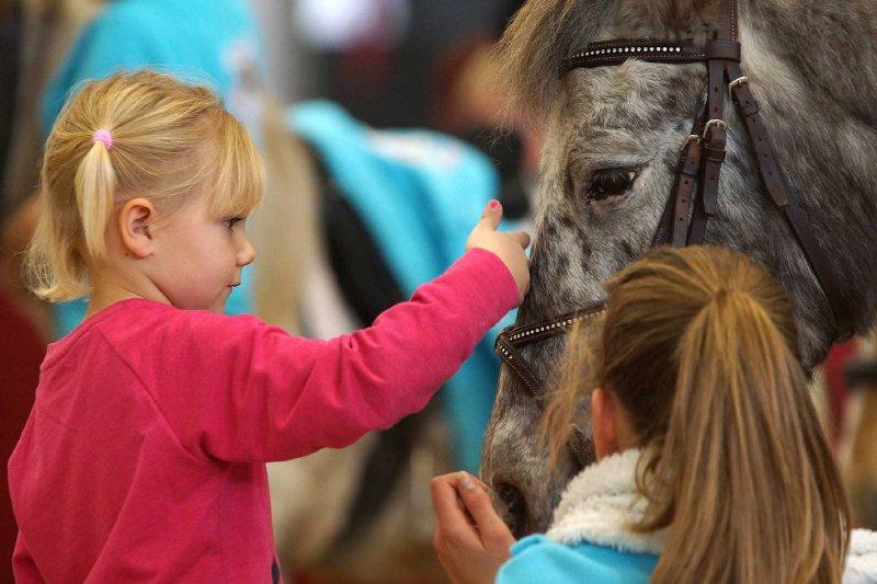 Schon Kinder sollten den richtigen Umgang mit den Pferden lernen. Hier sieht man Nina, die Tochter von Österreichs Spitzenspringreiterin Julia Kayser, im liebevollen Umgang mit einem Pony. © Salzburg-Cityguide