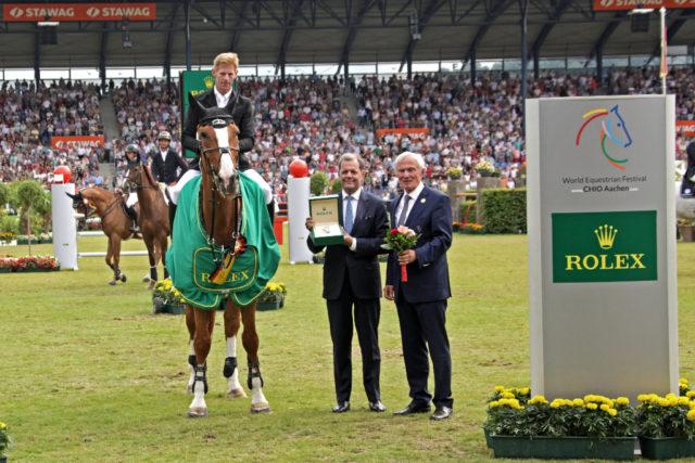 Dem Rolex Grand Prix-Sieger Sieger Marcus Ehning gratulieren Rafael Rolli, Geschäftsführer Rolex Deutschland GmbH, und ALRV-Präsident Carl Meulenbergh. © CHIO Aachen/ Michael Strauch
